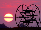 Farm Equipment is Silhouetted by a Setting Sun Photographic Print