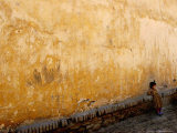 A Little Girl Rests at a Wall Photographic Print