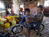 Children Play with a Bicycle Inside a Chicken Shed at Bobokan Tempel Village Photographic Print