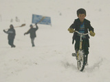 A Young Afghan Boy Rides His Bicycle on a Snow Covered Street Photographie