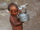 A Boy in a Slum Along the Yamuna River in the Older Part of New Delhi Drinks Water from a Tea Pot Photographic Print