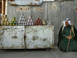 A Palestinian Sits Near the Stand of a Street Seller Displaying Goods for Sale Photographic Print