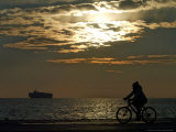 A Woman Rides Her Bicycle During the Sunset Photographic Print