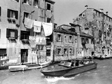 A Man Takes His Boat Through the Canal Photographic Print