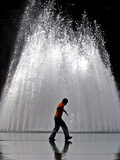 A Boy Crosses Over a Fountain Photographic Print