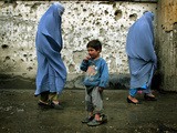 A Young Afghan Refugee Boy Stands in a Pair of Adult's Shoes Photographic Print