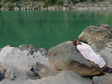 A Hindu Pilgrim Rests Along the Peaceful Bank of the Ganges River Near Rishikesh Photographic Print