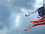 A Shredded U.S. Flag is Blown by the Wind Photographic Print