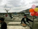 An Afghan Boy Sits on a Grave Plot and Sells Balloons and Eggs as Others Relax Photographic Print
