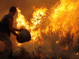 A Local Resident Throws a Bucket of Water on a Forest Fire Photographic Print