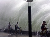 Residents on Their Bicycles Pause to Admire at Giant Waves Slamming against a Sea Wall Photographic Print