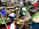 Small Wooden Boats Loaded with Fresh Produce Gather Along a Canal Photographie