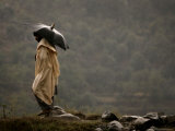 A Pakistani Man Tries to Protect Himself from Heavy Rain Photographic Print