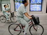 Workers Pedal Bicycles Past a Securities Firm in Tokyo Photographic Print
