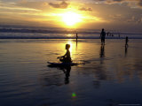 An Indonesian Boy Sits on His Surfboard at Sunset Photographic Print