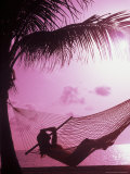 Woman Relaxing in a Hammock on the Beach at Sunset Photographic Print by Bill Bachmann