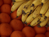 Close-up of a Pile of Fresh Ripe Bananas and Juicy Oranges in a Mesh Net Photographic Print