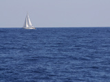 An Expanse of Blue Sea with a Single White Sailboat Photographic Print