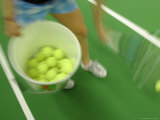 A Blurry Woman with a Bucket of Tennis Balls and Racket Photographie