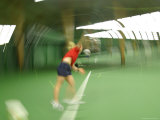 A Blurry Woman Serving a Tennis Ball on a Green Court Photographie