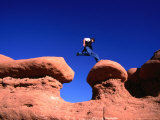 A Man Jumps onto a Hoo-Doo Formation in Goblin Valley, Goblin Valley State Park, Utah, USA Photographic Print by Cheyenne Rouse