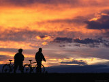 Two People and Bicycles Silhouetted at Sunset, Tiszafured, Hungary Photographic Print by David Greedy