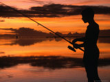 The Silhouette of a Boy Fishing at Sunset in One of the Lagoons Around the Island, Cook Islands Photographic Print by Dallas Stribley