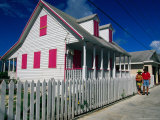 A Couple Shop along a Colourful Street in Abaco, Bahamas Photographic Print by Greg Johnston