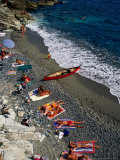 Sunbathing on Pebble Beach, Italy Photographic Print by Wayne Walton