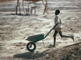 Boy Running with Wheelbarrow, Burkina Faso Photographic Print by Eric Wheater