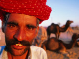 Rajput Camel Driver at Pushkar Camel Fair, Looking at Camera, Pushkar, India Photographic Print by Paul Beinssen