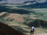 Trekker Looking Out at Hills and Meadows Outside of Kochkor, Kyrgyzstan Photographic Print by Anthony Plummer