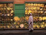 Man Walking Past Brass Platters And Trays, Luxor, Egypt Lámina fotográfica por Anders Blomqvist