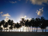 Sun Setting Behind Palm Tree Lined Shore of West Coast, Cook Islands Photographic Print by Manfred Gottschalk