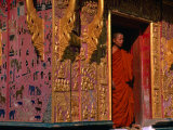 Buddhist Monk Standing in Doorway of Wat Xieng Thong, Luang Prabang, Laos Photographic Print by John Banagan