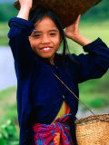 Portrait of Girl Balancing Basket of Herbs, Muang Ngoy, Laos Photographie par Anthony Plummer