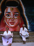 Local Men Read Newspapers in Front of Painted Shutter, Kozhikode, Kerala, India Photographic Print by Greg Elms
