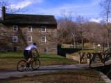 Man Cycling Past Building in Rock Creek Park, Washington Dc, USA Photographic Print by Rick Gerharter