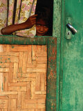Young Child Peeking Out from Behind Curtain at Watukarare, Sumba, East Nusa Tenggara, Indonesia Photographic Print by Paul Kennedy