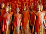 Statues Draped in Saffron in the Royal Funerary Carriage House at Wat Xieng Thong, Laos Photographic Print by Ryan Fox