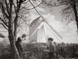 Men Chopping Wood Near a Windmill, 1920s Photographic Print