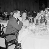 Elizabeth Taylor Sitting on a Dinner Table with Other People, March 1968 Photographic Print
