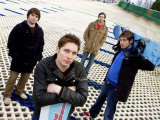 Music Group Snow Patrol Pictured on a Dry Ski Slope with Snowboards Photographic Print