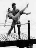 Actor Steve Reeves on a Pier by the Sea, Carrying Woman in a Bikini and Headscarf Lámina fotográfica