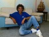 David Essex, med jeans og blå t-shirt, sidder på gulvet op ad en sofa Fotografisk tryk