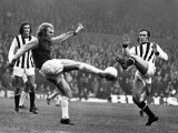United West Ham's Bobby Moore Kicks the Ball Clear from Jeff Astle Photographie