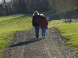 Mother and Daughter Arm in Arm Walking on a Pathway Photographic Print by Todd Gipstein