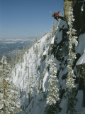 Man Rappels Down Red Mountain with a Snowboard on His Back Photographic Print by Mark Cosslett