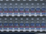 Rows of Fuji Brand Mineral Water Sit on Shelves Waiting to Be Sold Photographic Print by Karen Kasmauski