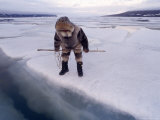 An Inuit Hunter Waits For Seals on an Ice Floe Photographic Print by Gordon Wiltsie